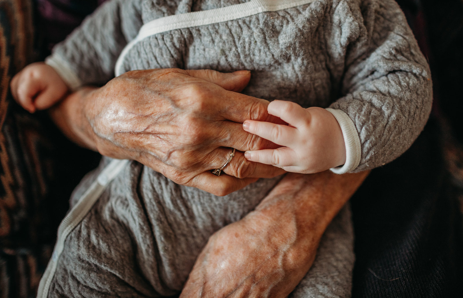 close up image of infant hand holding elderly hand in framingham ma