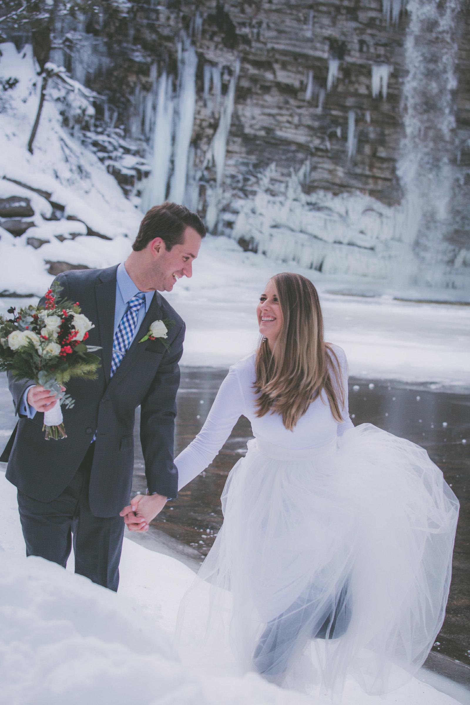 Bride and groom smiles and walks together through snow during their Upstate New York elopement.