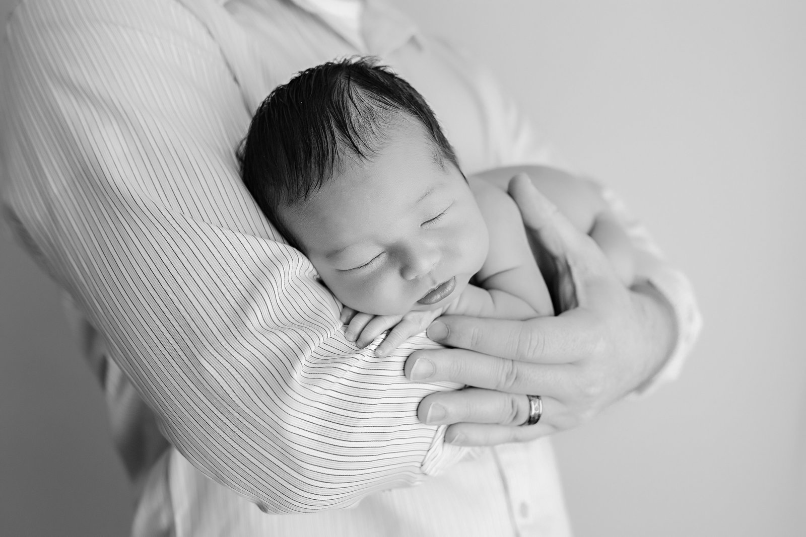 Asian baby in father's arms