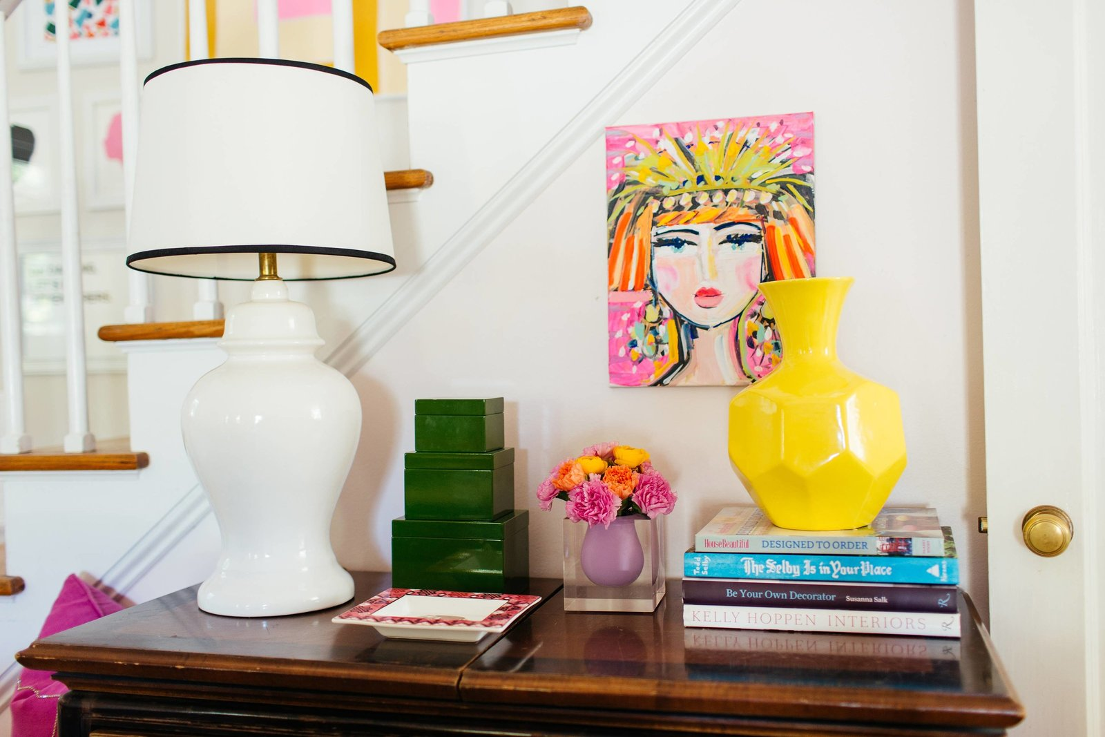 A side table with a white lamp and accessories.