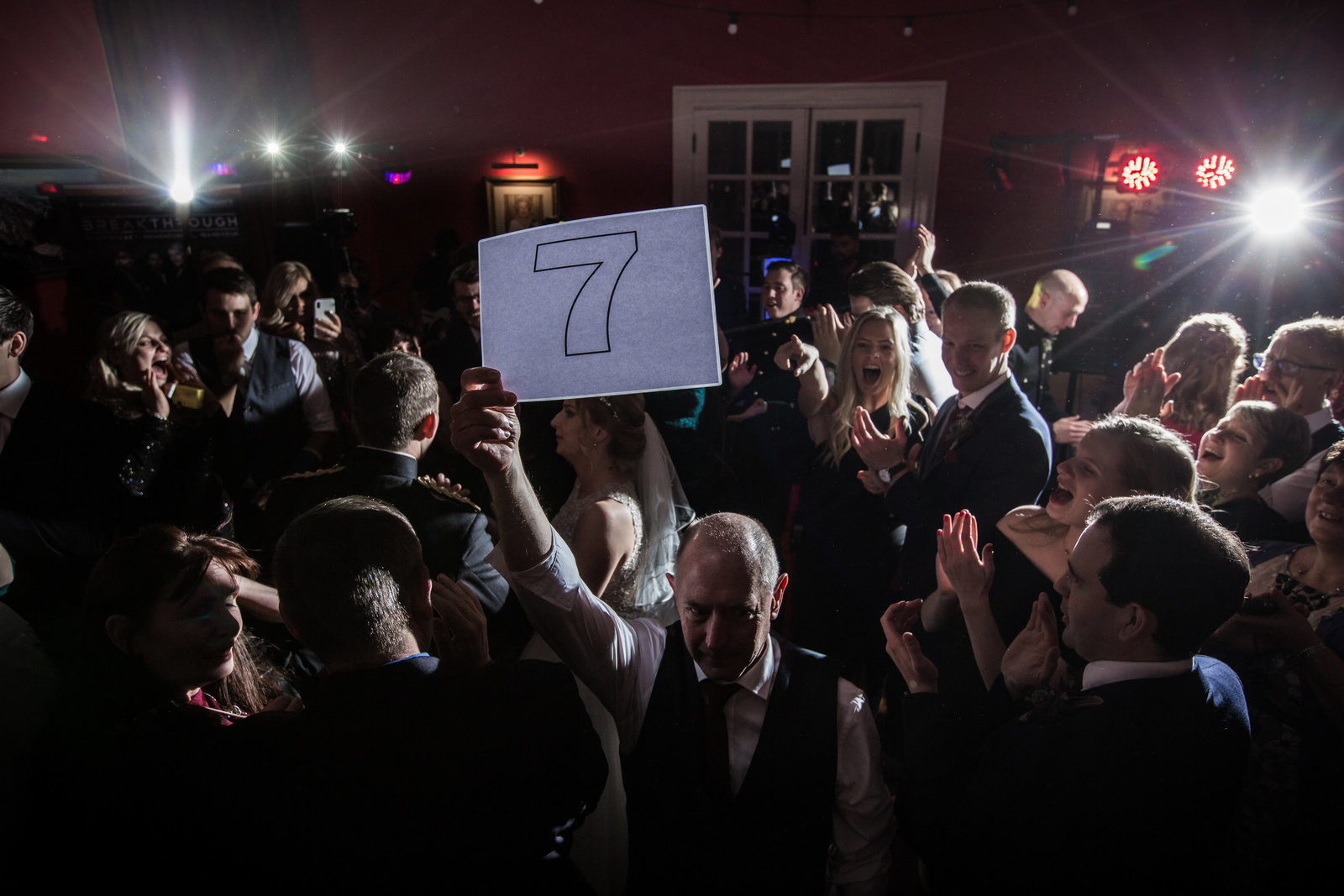 During the dancing at a wedding, the Brides Dad holds up the number 7 on a card in the style of an ice skating judge, the guests all laugh.