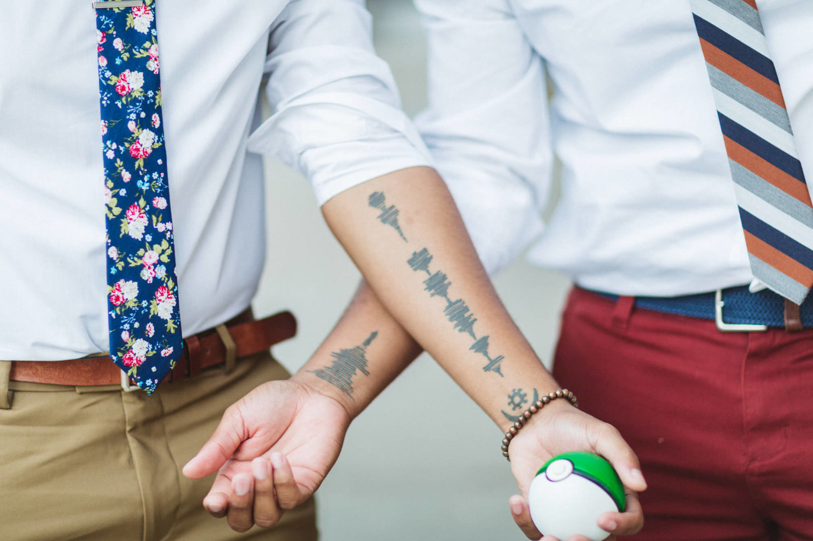 gay couple showing off their matching frequency tattoos on san francisco engagement shoot