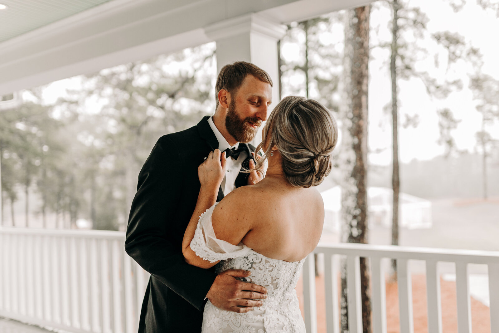 Bride and groom share embrace during their first look at White Oak Road wedding venue in Appling, Ga