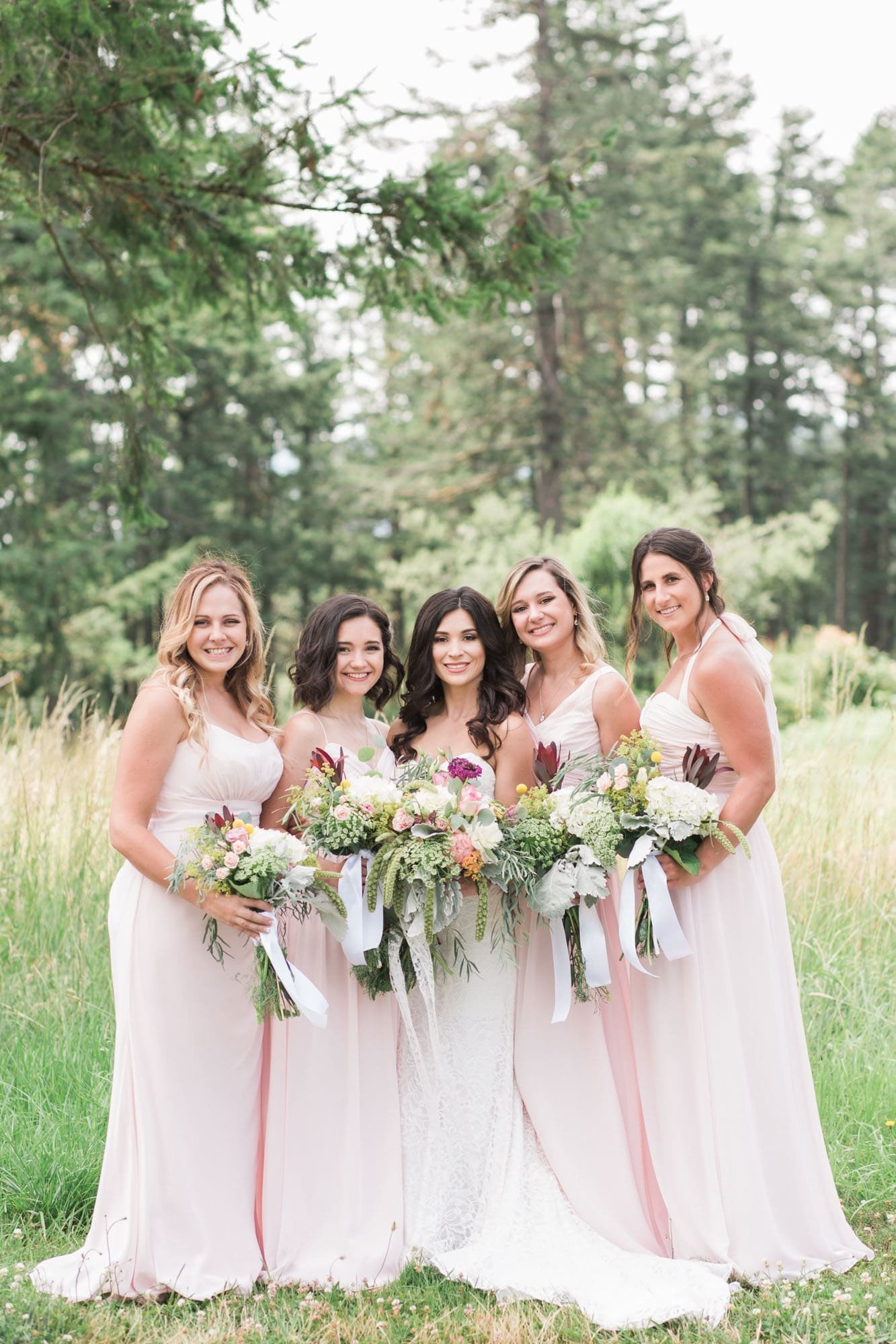 Bridesmaids pose for photos at an outdoor Oregon wedding venue