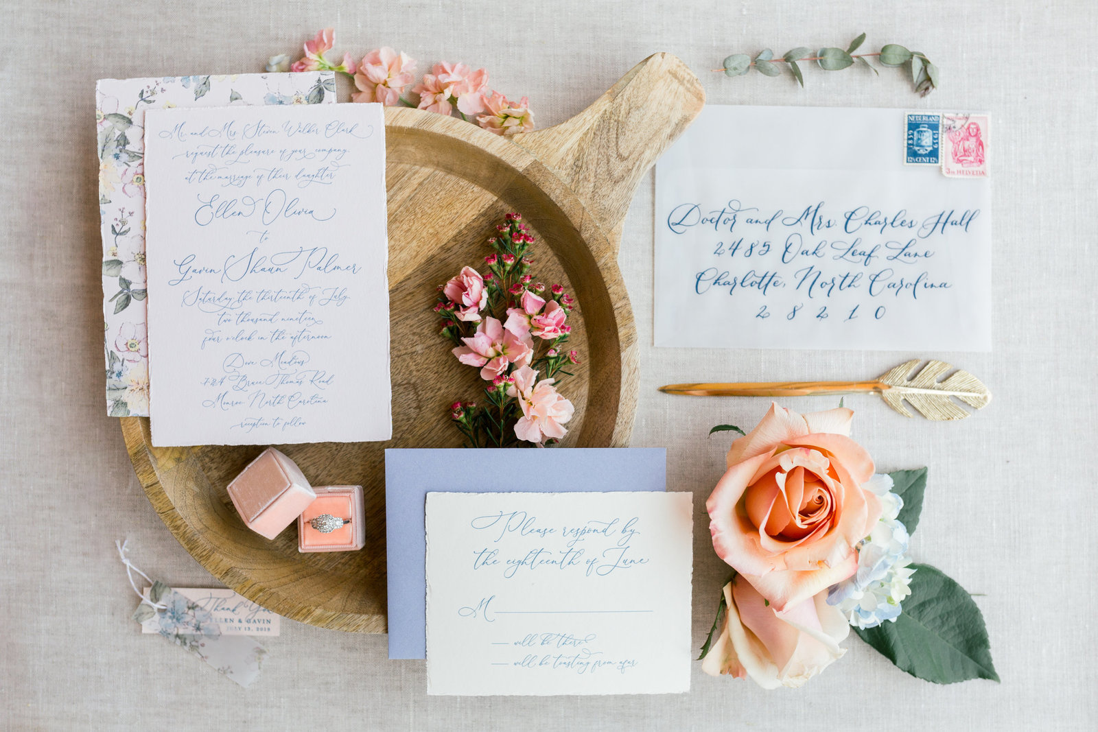 Custom invitation suite with vintage watercolor florals, deckled edges, and a vellum envelope