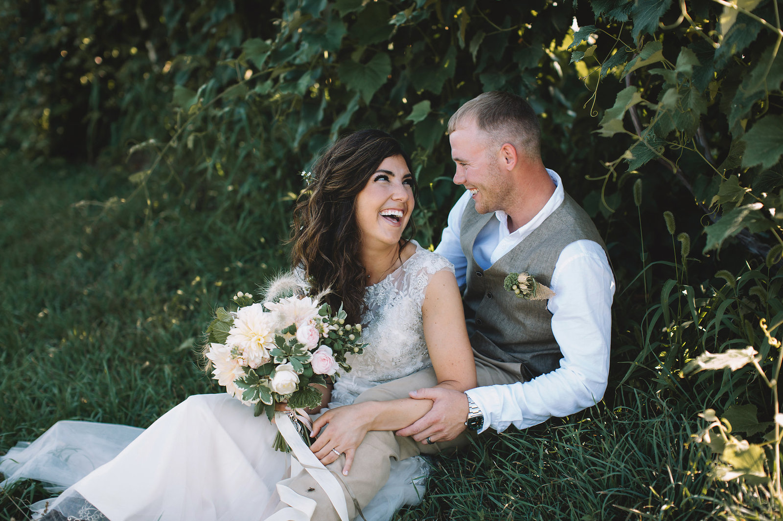 Bride and groom sitting in a vineyard kissing in Iowa