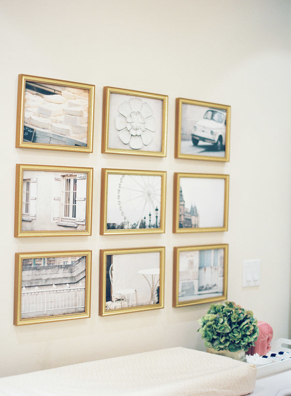 A grid gallery wall of fine art and photos above a changing table.
