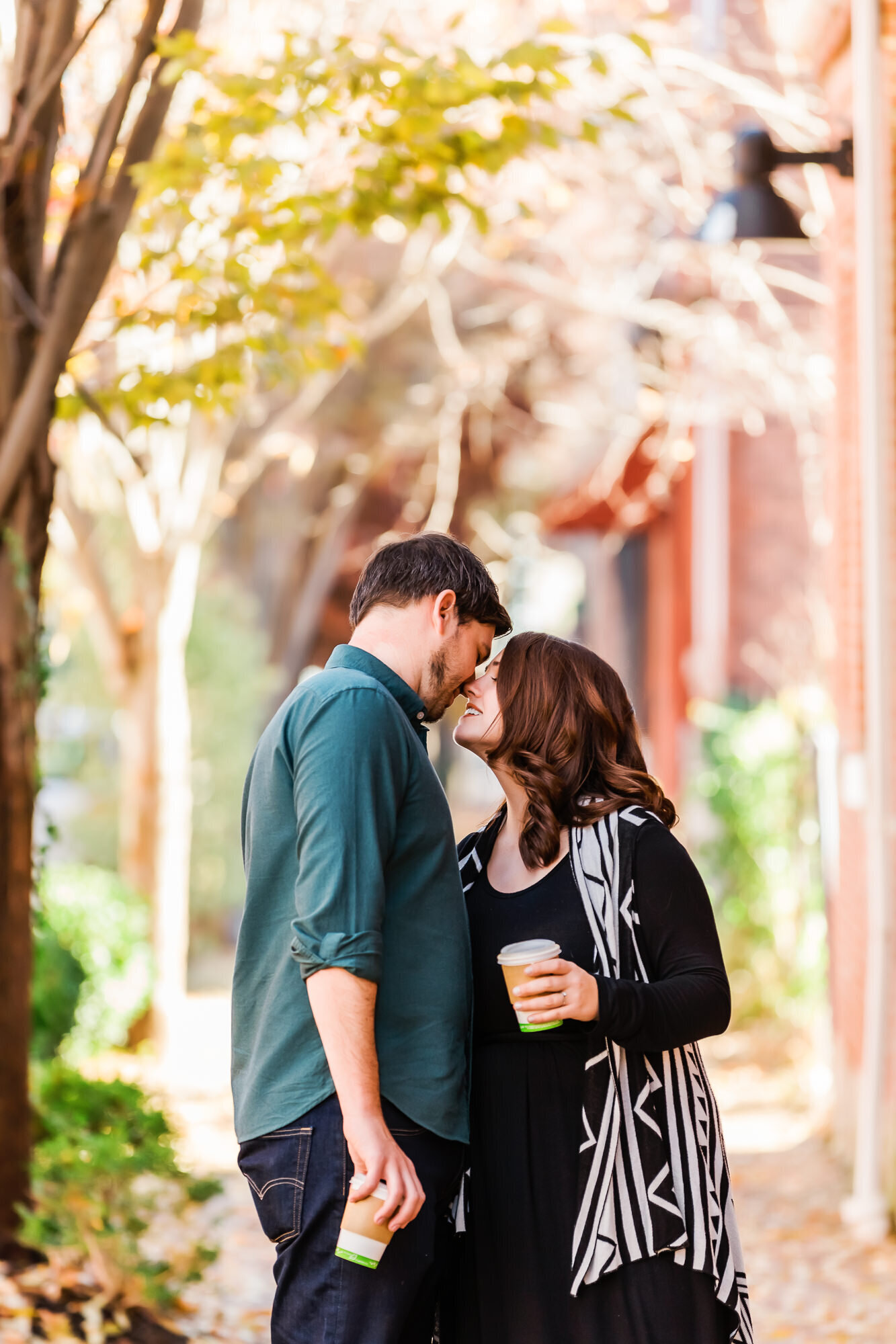 Engaged couple kissing on the sidewalk during their coffee date engagement session in St. Louis
