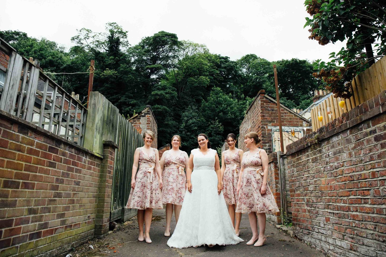 Bride and pink bridesmaids smiling down a brick alleyway before her Norwich wedding