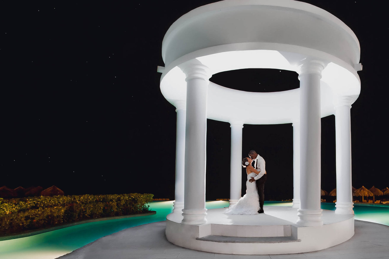 Bride and groom pose at night under the gazebo, Jamaican Destination Wedding, Iberostar Rose Hall Suites, Montego Bay