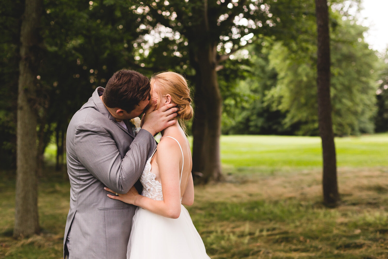 bride and groom kiss during candid portraits on golf course ohio