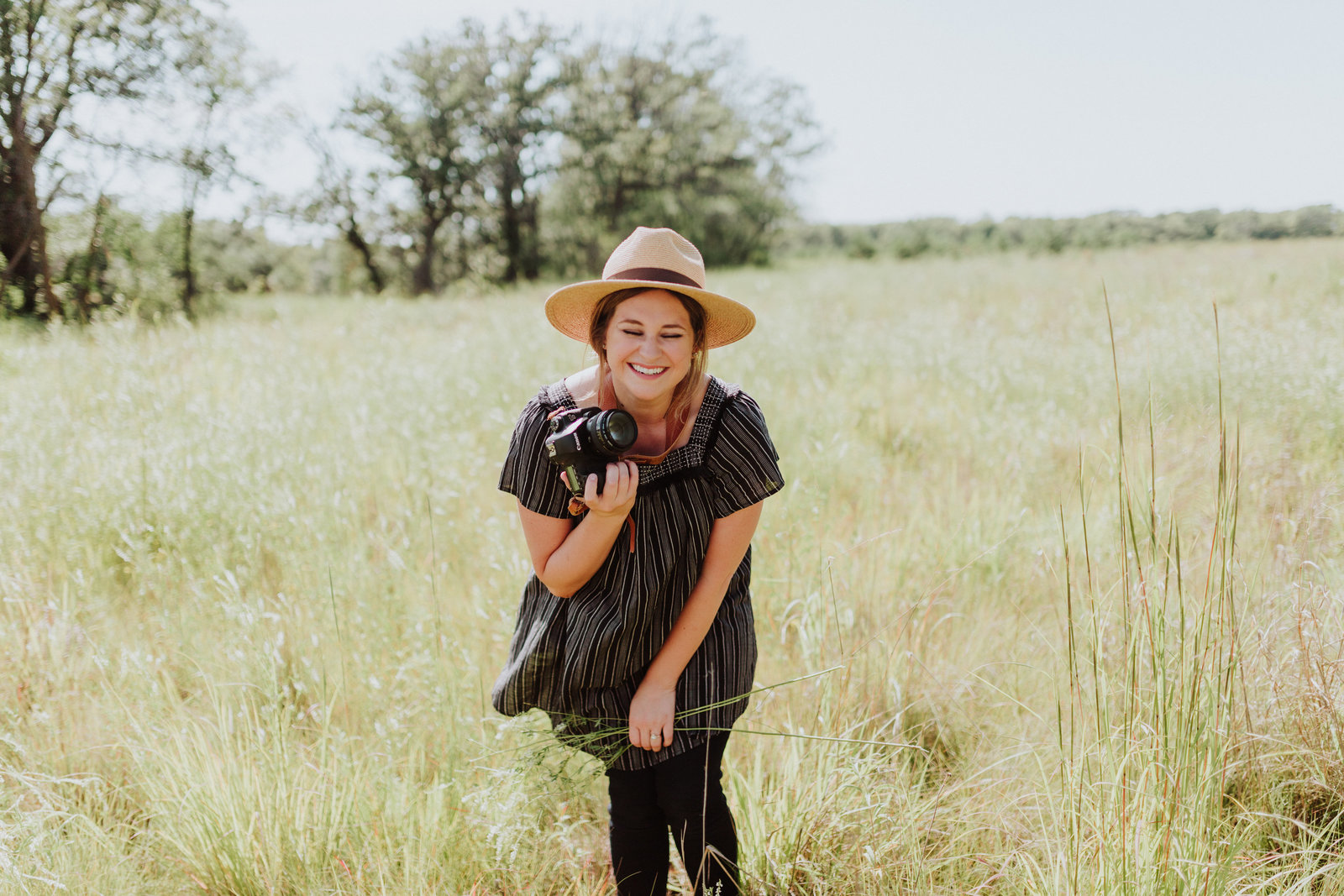 Girl laughing in field holding Canon camera