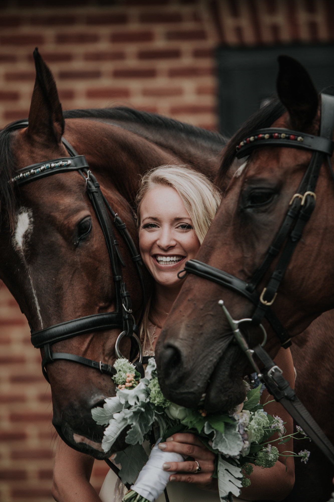 bride poses with her horses at her farm wedding in PA