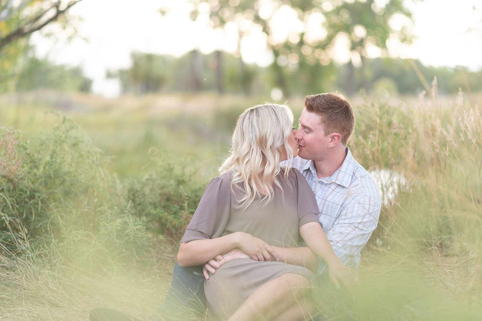couple sitting in grassy field during engagement photos