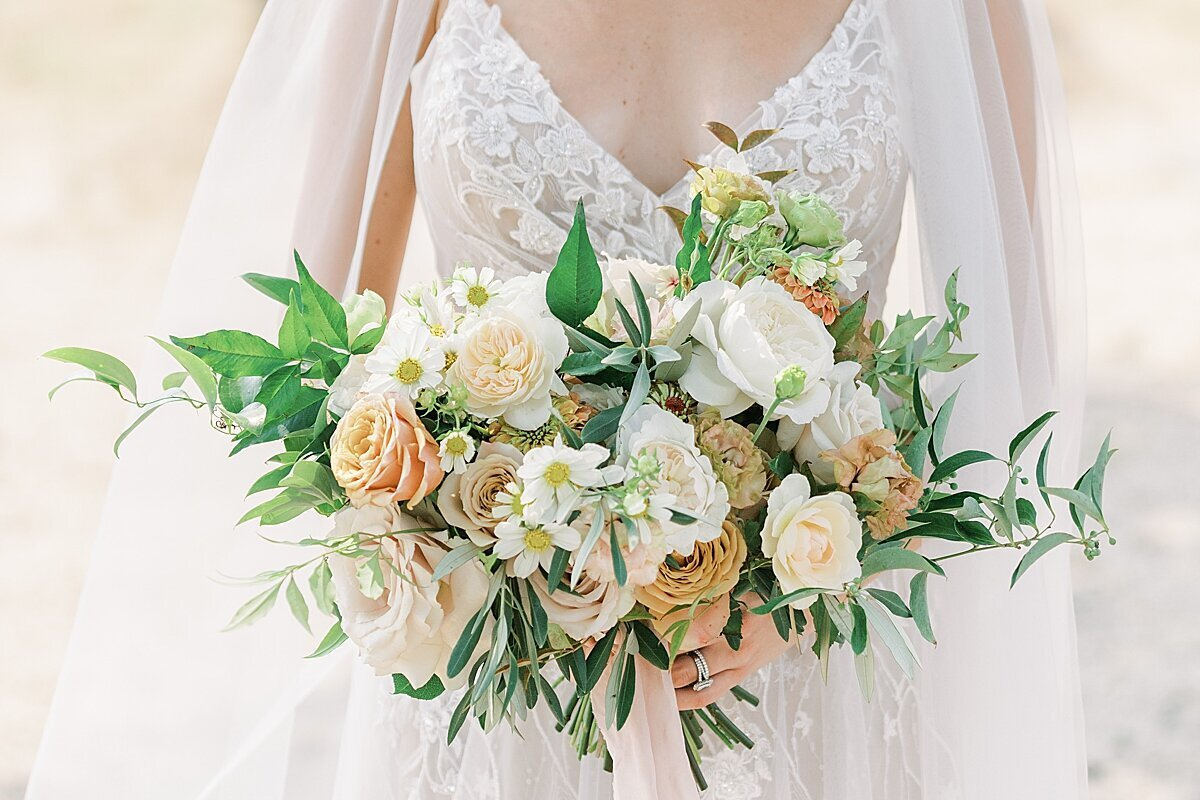 Bride holding her peach and white floral boquet
