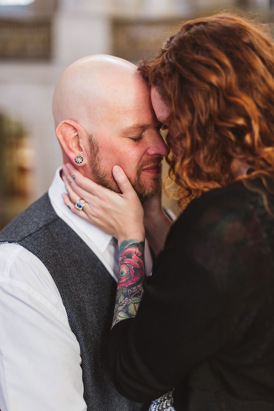 tattooed couple holding each other close on staircase