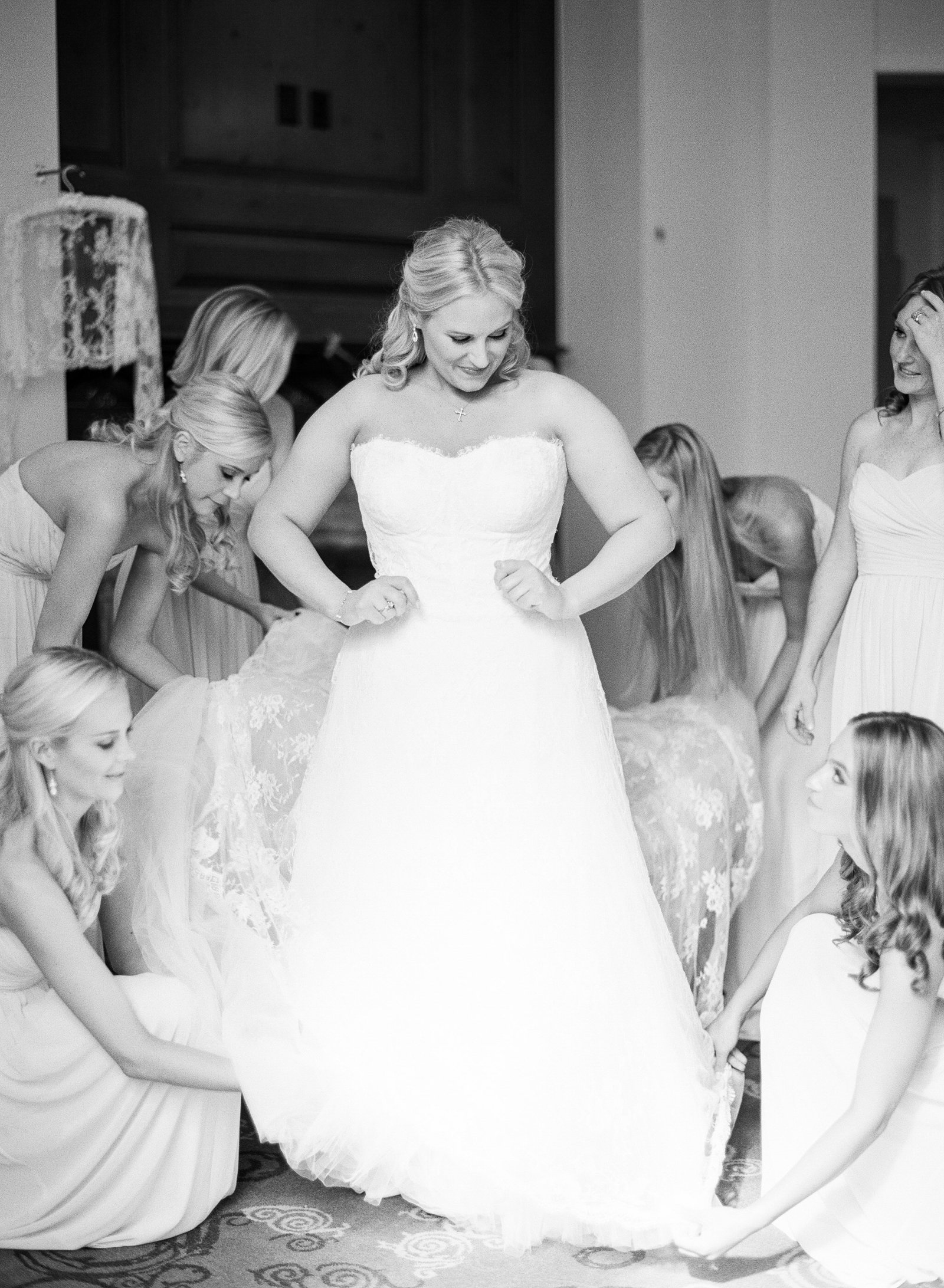 bridesmaids help their sweet bride get dressed before her wedding