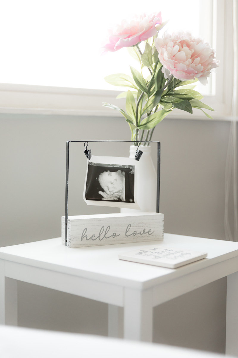 Ultrasound pictures and flower on side table in front of nursery window