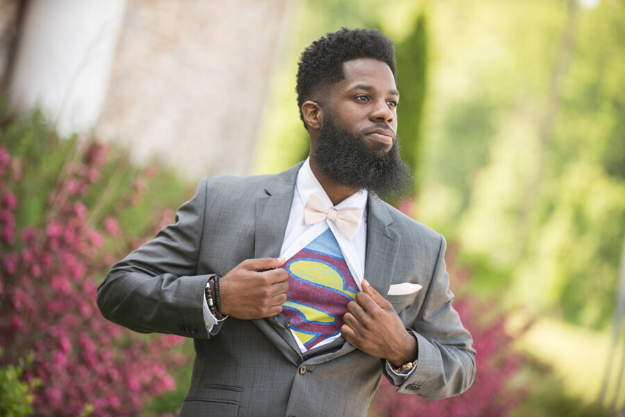 Groom wearing superman shirt under suit