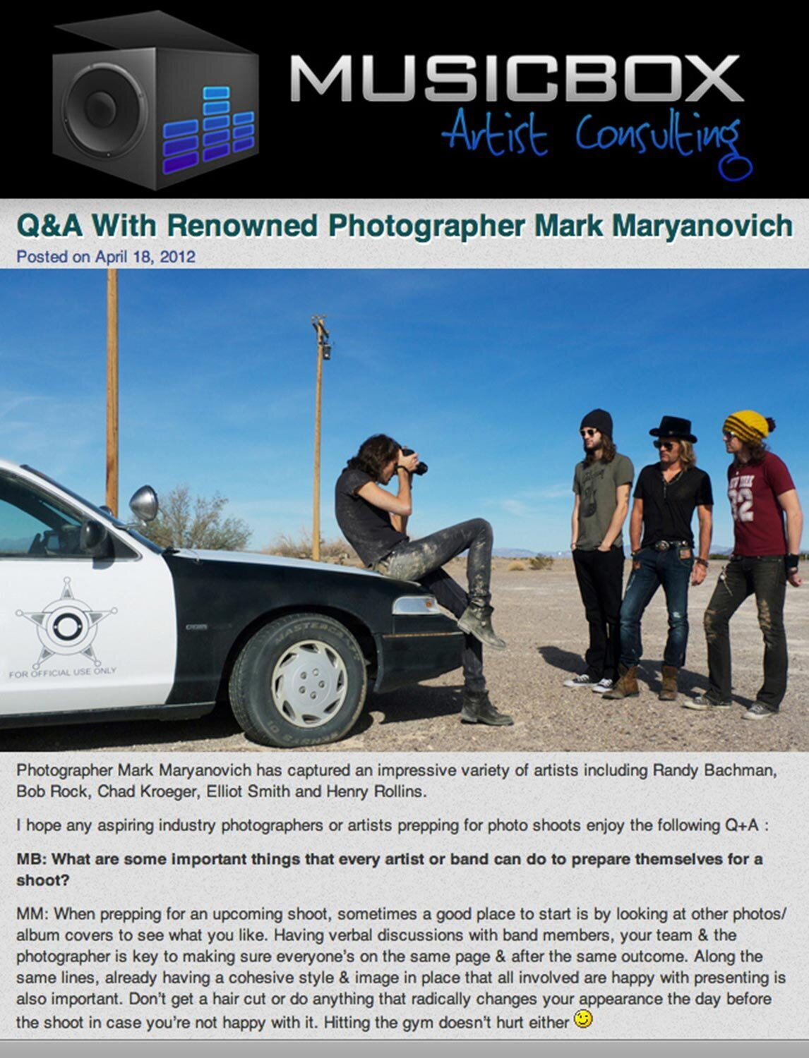 Interview with LA Photographer Mark Maryanovich Publication Musicbox Artist Consulting page 1 behind the scenes photo Mark taking portrait of three band members while sitting on hood of car
