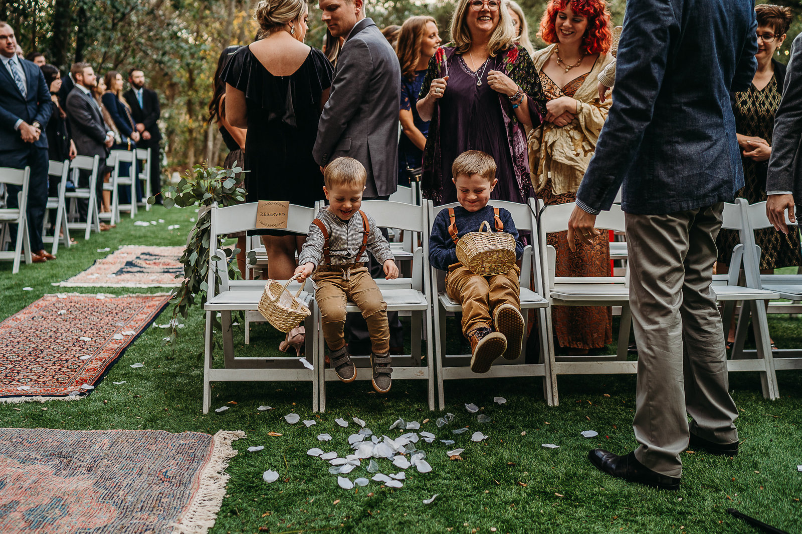 two ring bearers laugh and drop petals during wedding ceremony