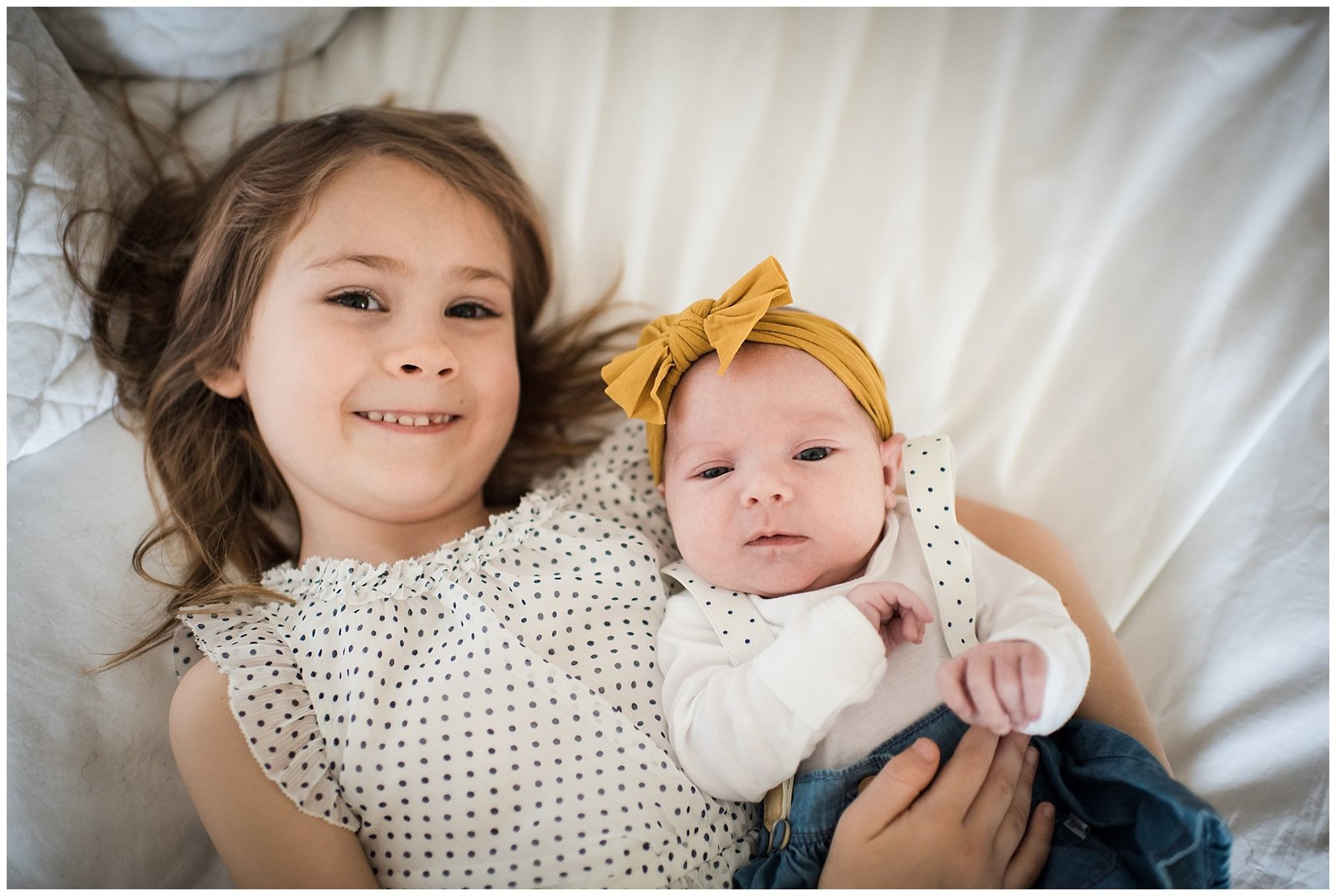 Big sister cuddling new baby sister on bed Emily Ann Photography Seattle Photographer