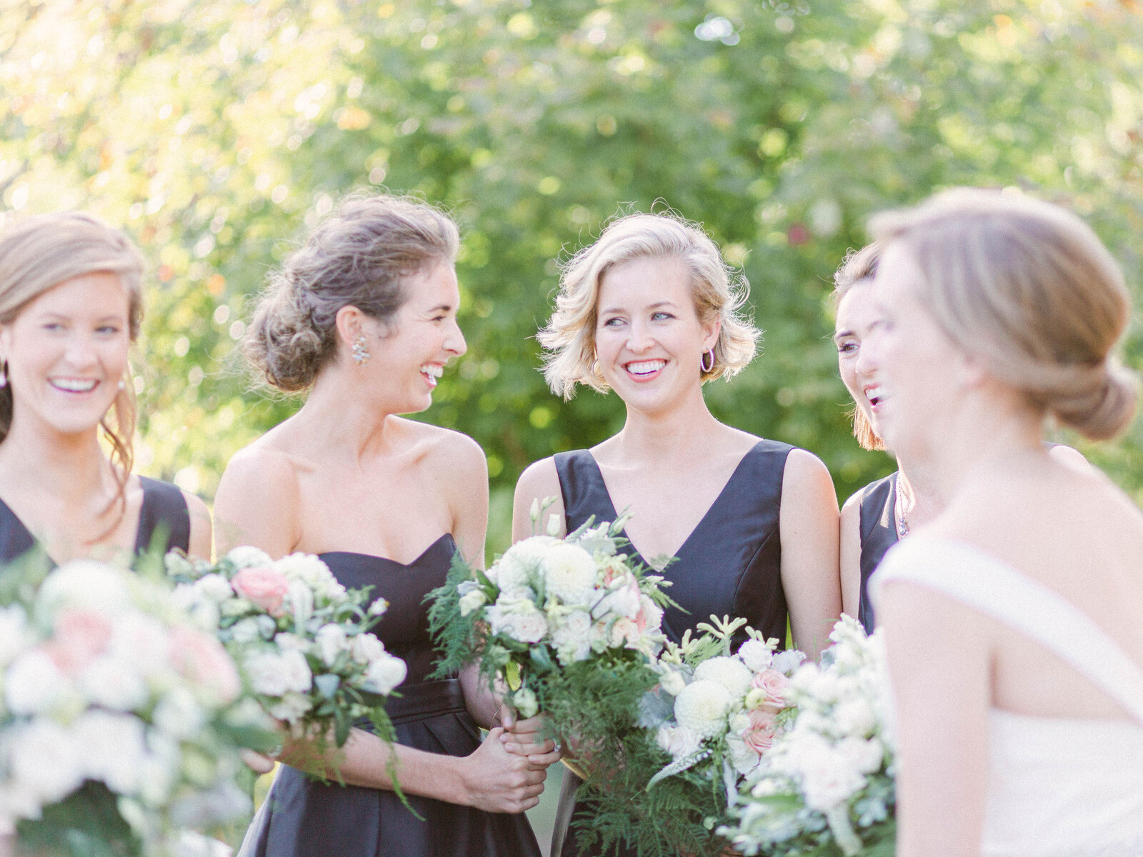 laughing bridesmaids with bouquets at wedding