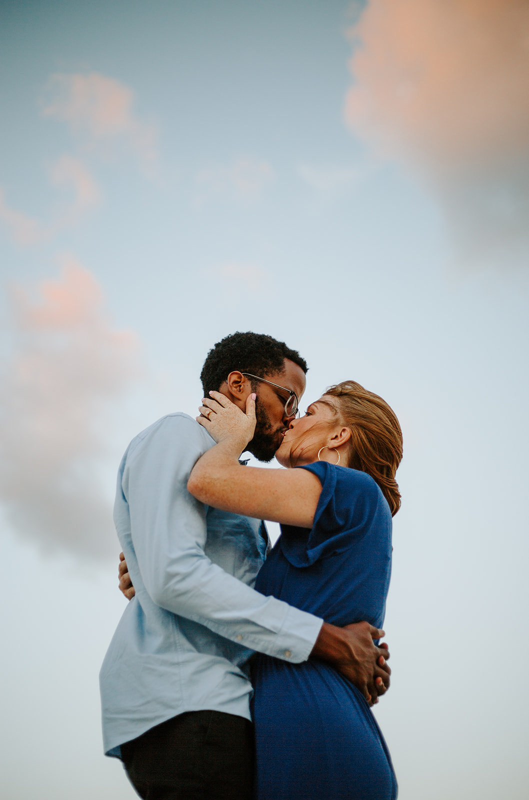 Couple holding in each other while kissing with the sky in the background during their Chicago engagement session