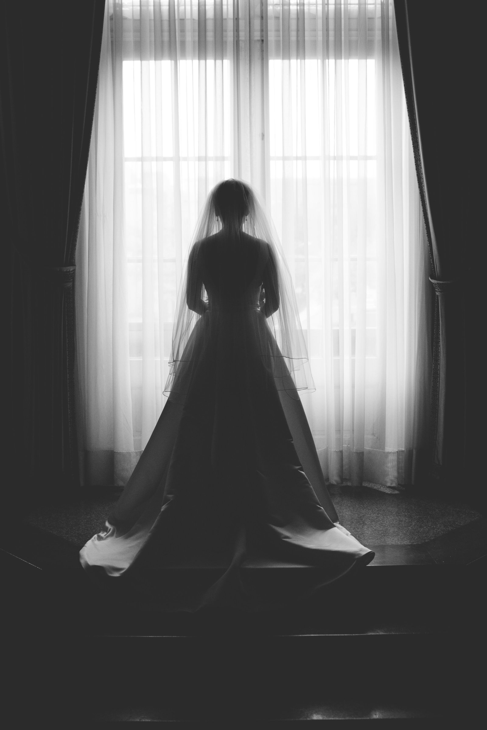 silhouette of bride in a full-size window