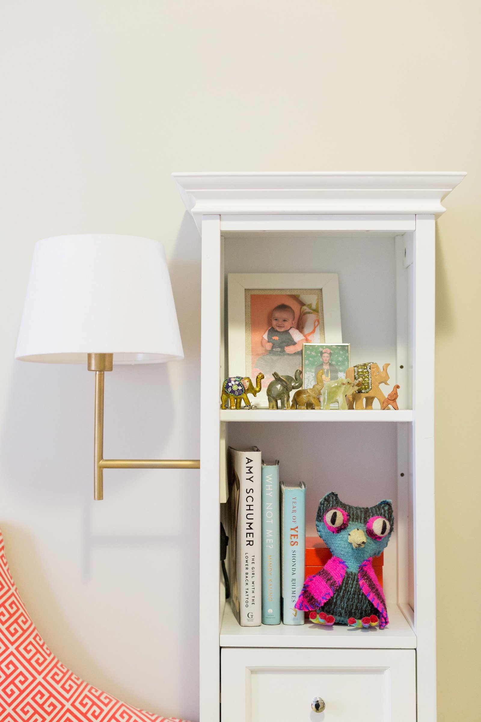 A bookcase with a gold sconce with white shade attached.
