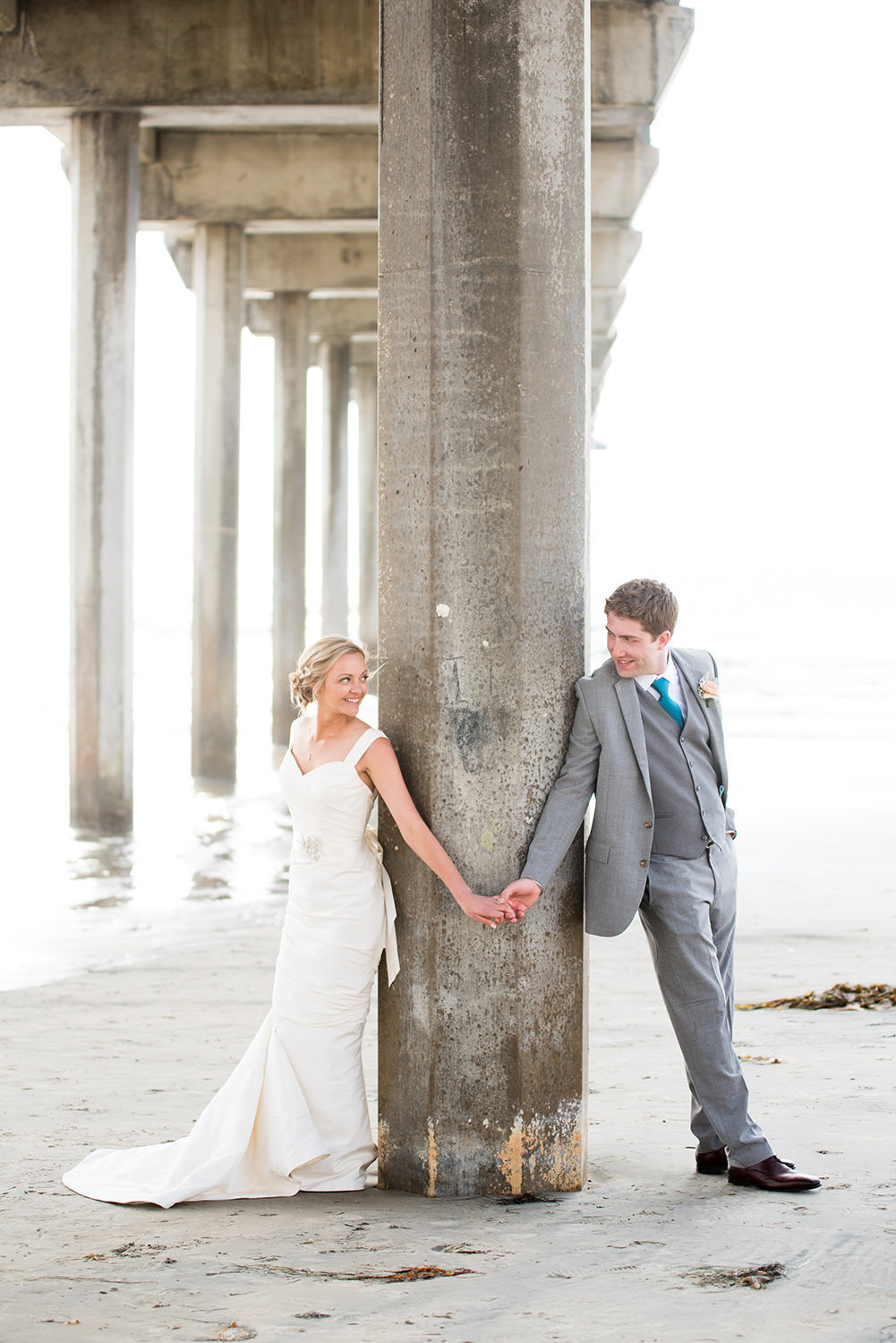 couple holding hands at scripps pier