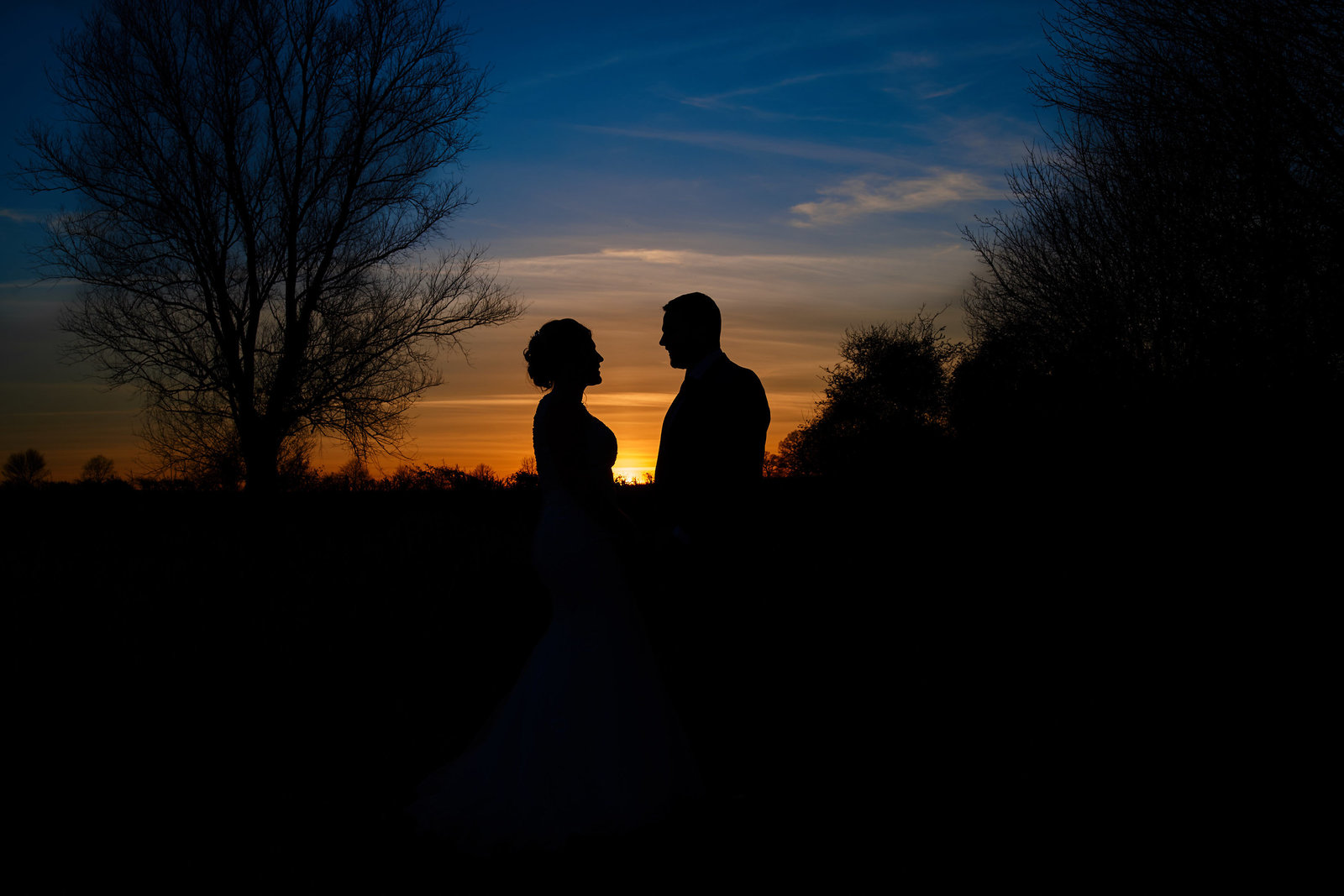 photograph at sunset of bride and groom silhouette at leez priory in essex