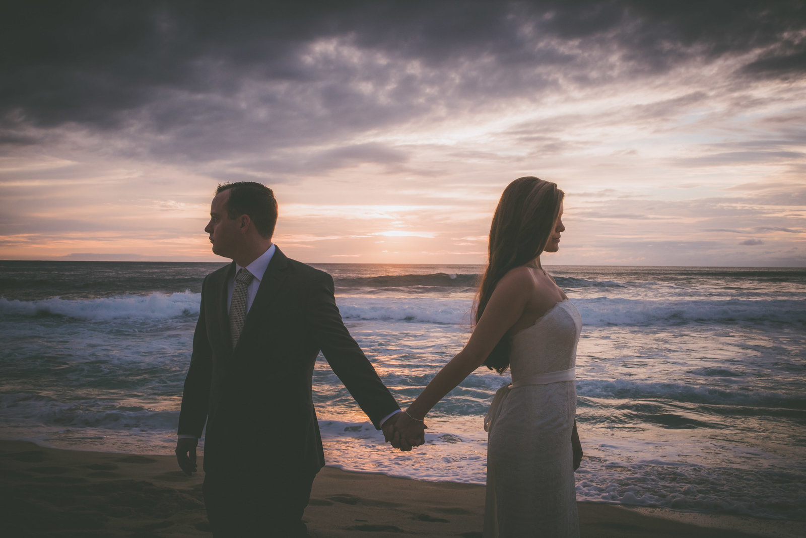 A couple hold hands during sunset on a Oahu beach.