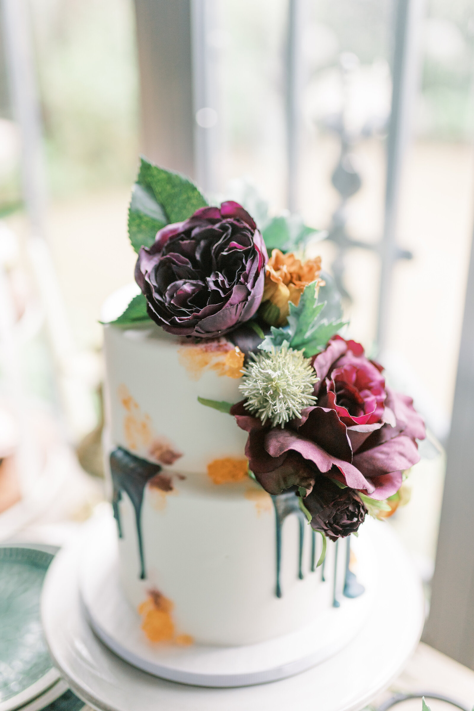 White wedding cake with dark purple flowers and orange accents