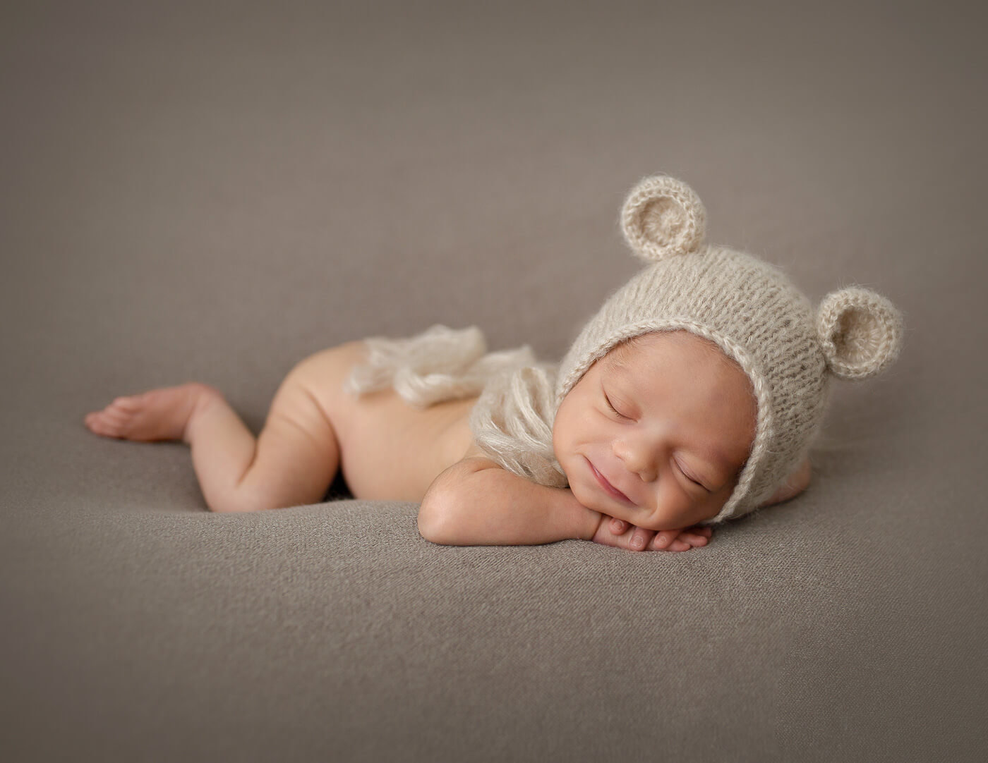 Handsome newborn in head on hands pose in our Rochester, NY studio.
