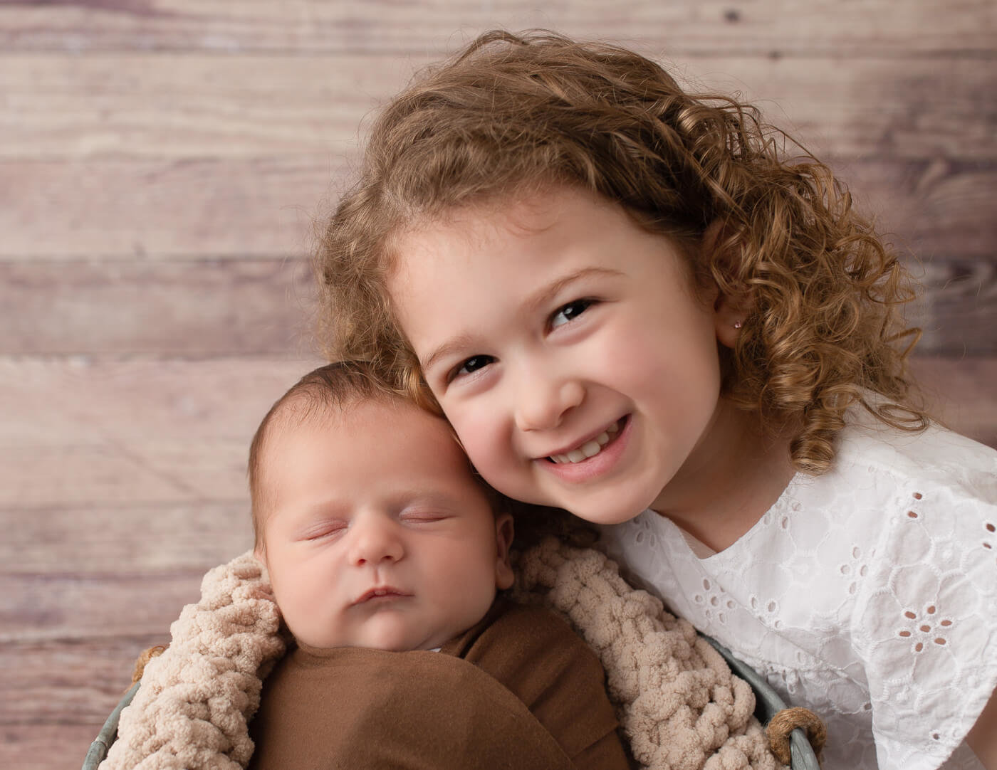 Newborn boy and big sister cheek to cheek in Rochester, NY studio