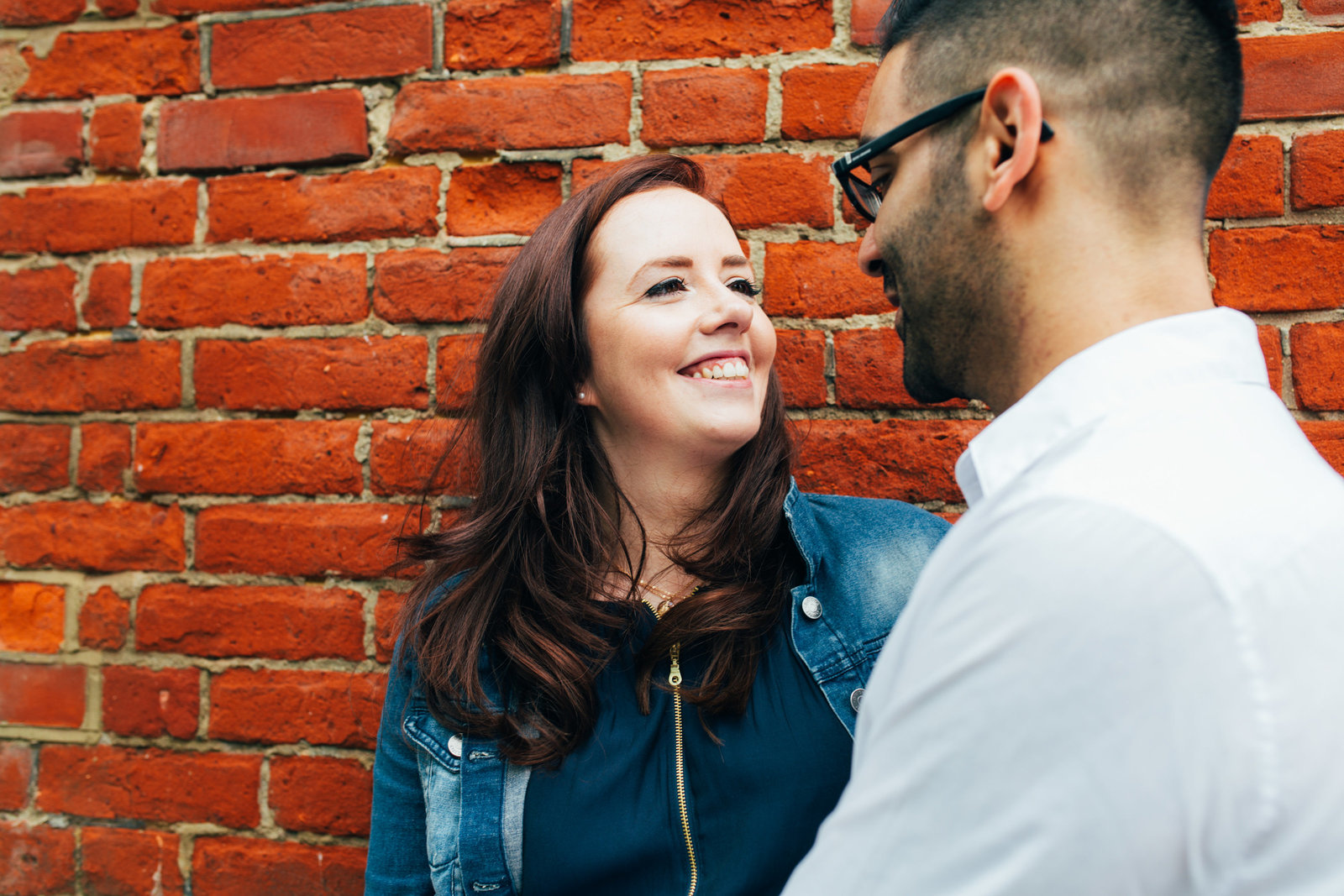 Laughing engaged couple lean against red brick wall for a natural couples photo