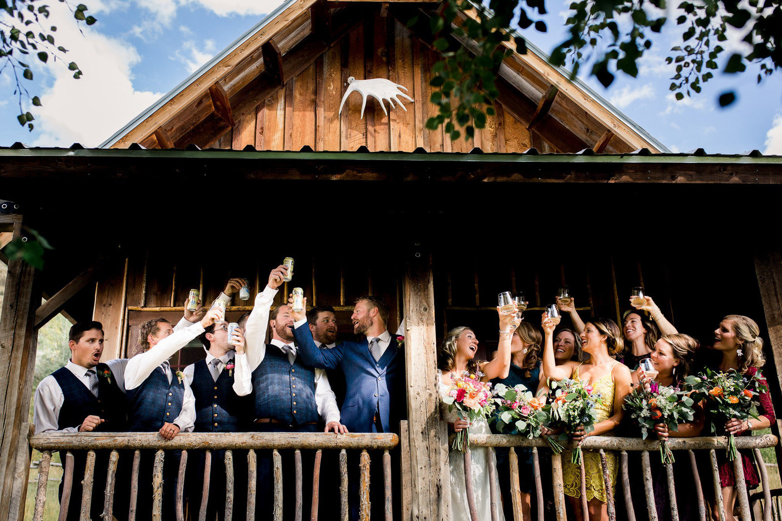 A bride and groom cheers with their closest friends on a barn's porch at a Jackson Hole Wedding
