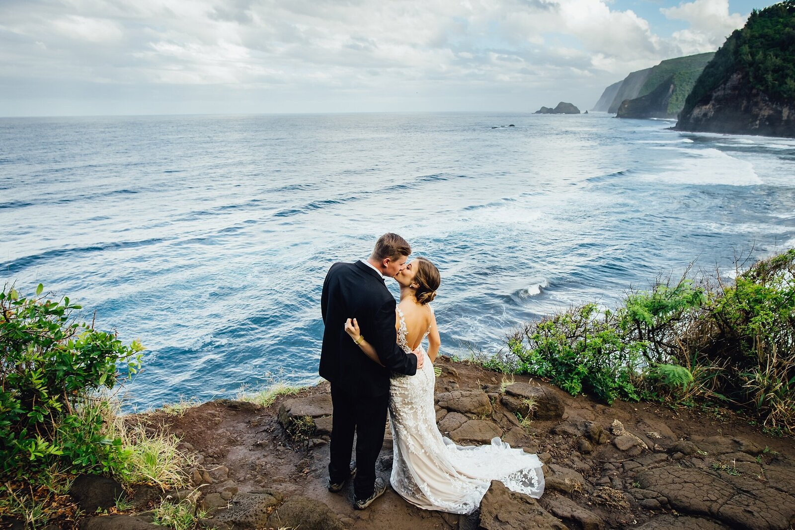 bride and groom kissing on cliff after their elopement at pololu valley