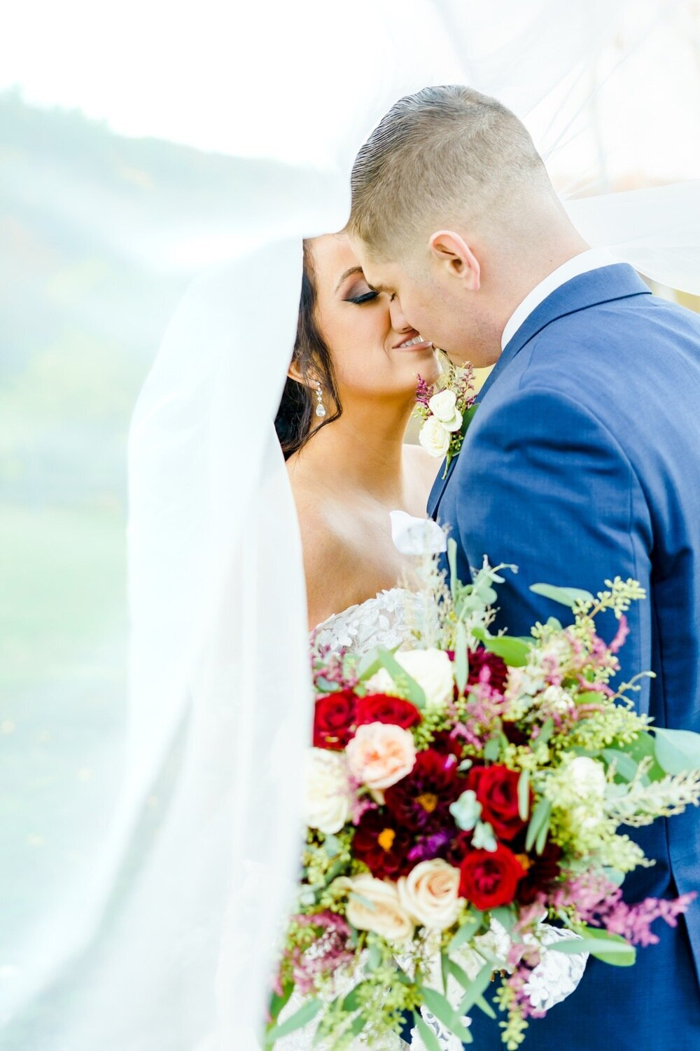 Bride and groom kissing with colorful bouquet