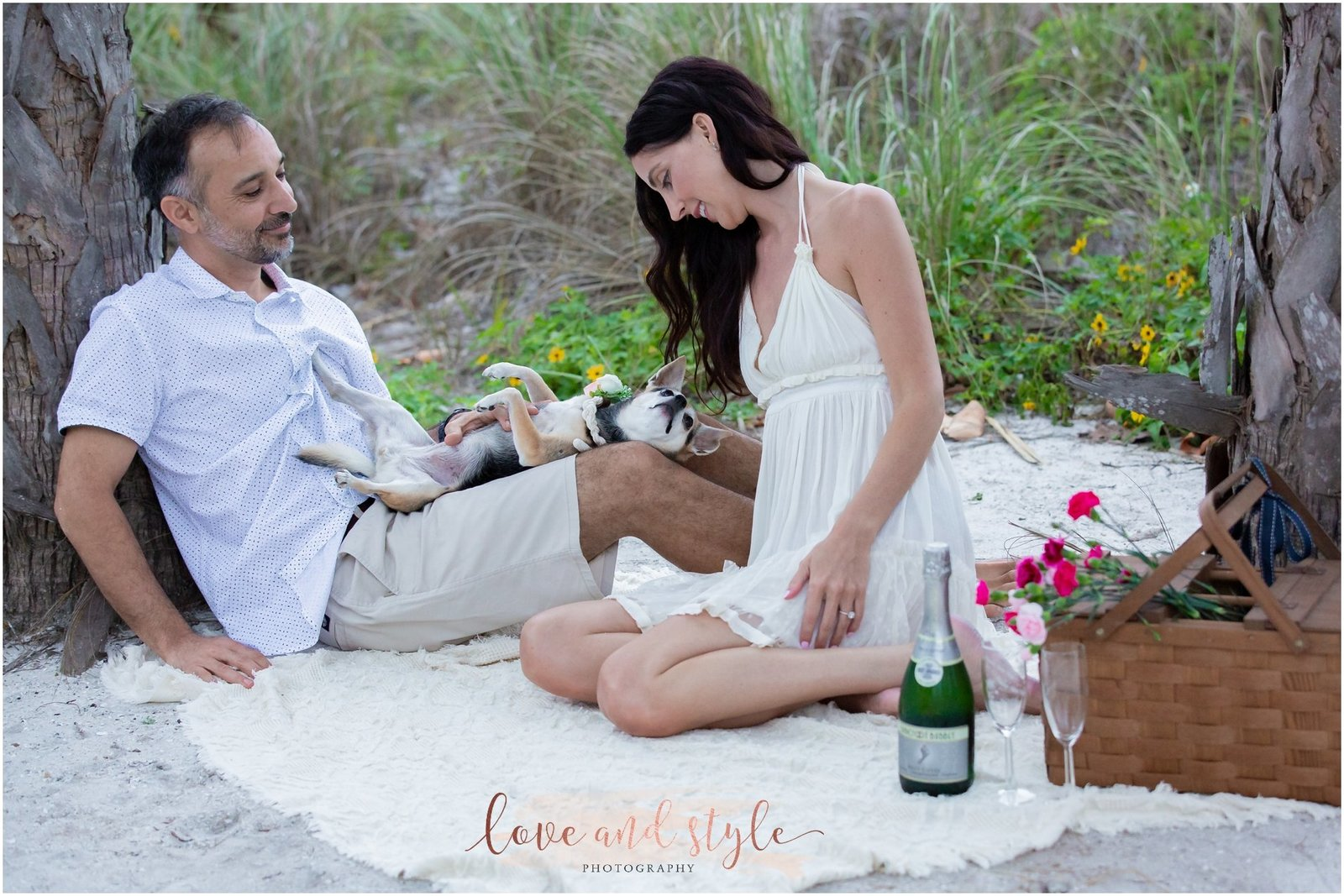 Engagement Photography on Anna Maria Island. Couple with their dog on a blanket having a picnic