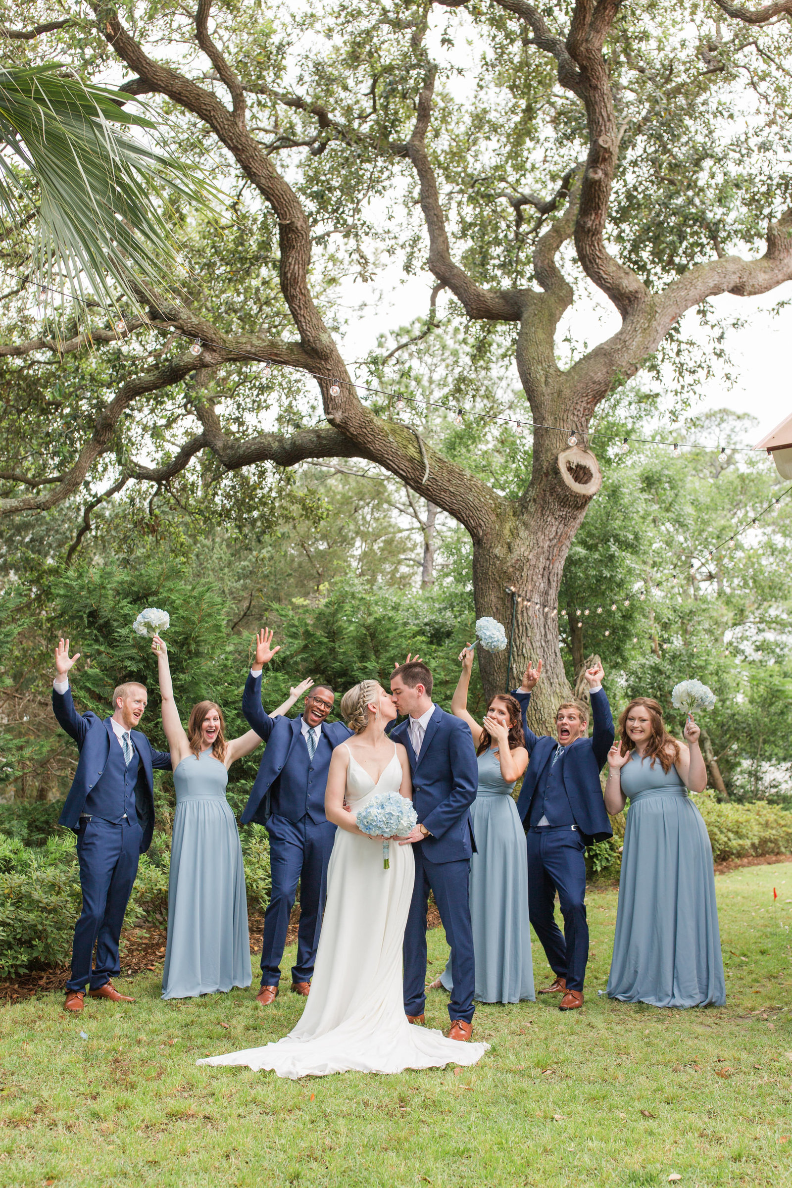 wedding party in blue dresses in front of oak trees cheering as bride and groom kiss