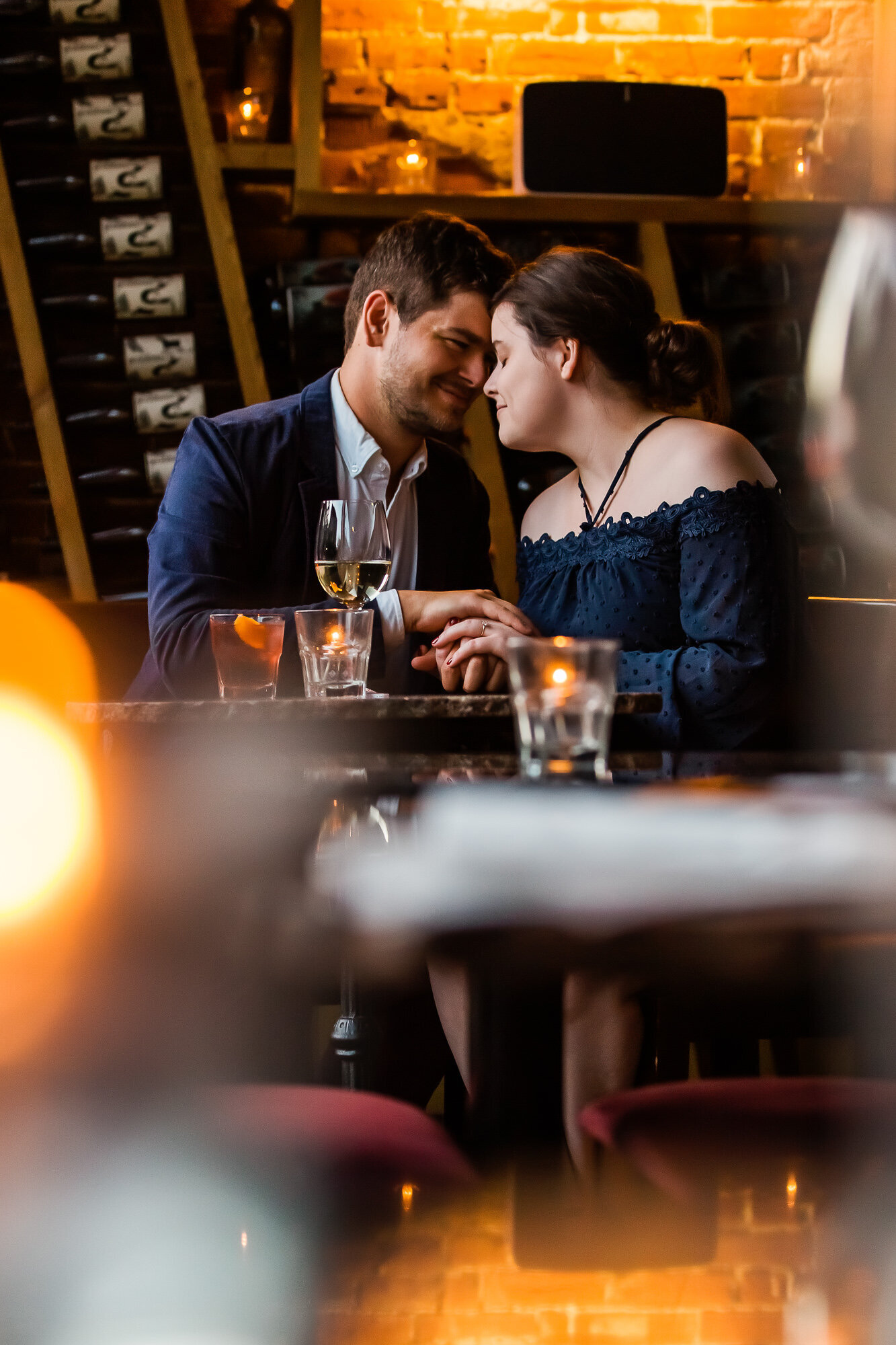 Romantic engagement photo of a couple having drinks together at Sasha's on Shaw in Saint Louis