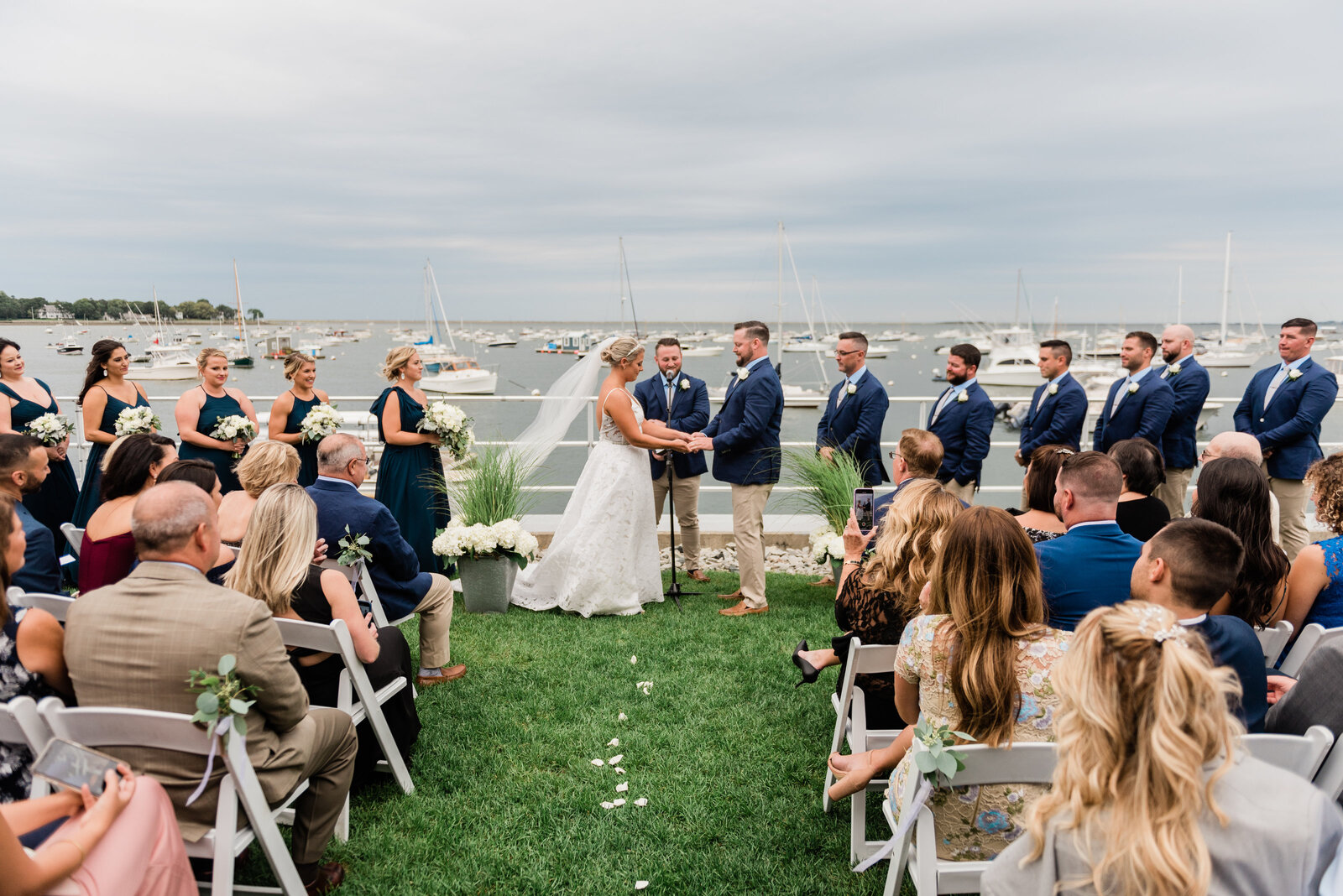 wedding ceremony on the lawn overlooking the water at the duxbury bay maritime school