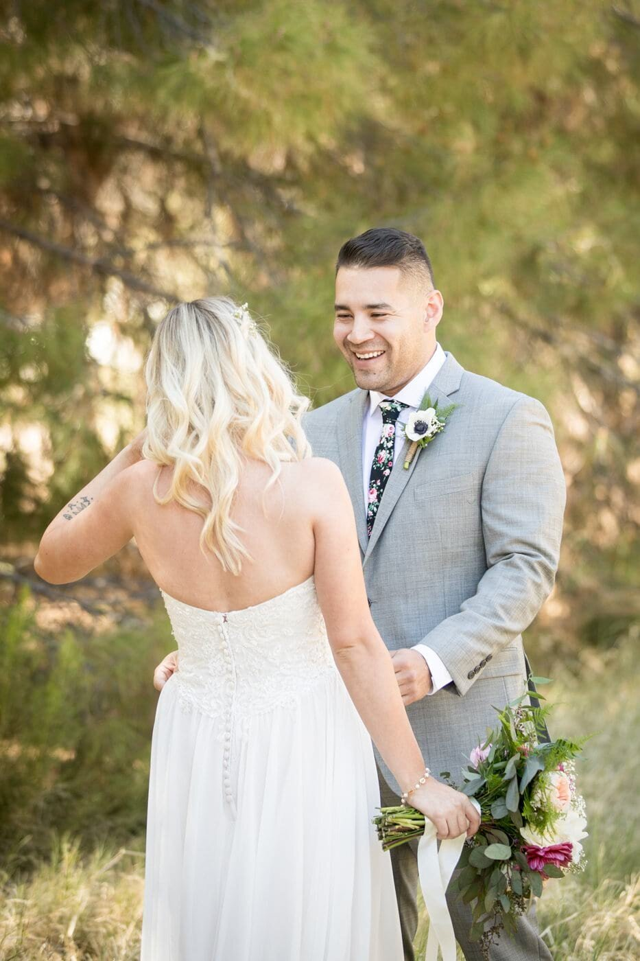 groom-smiling-at-bride-first-look-windmill-winery