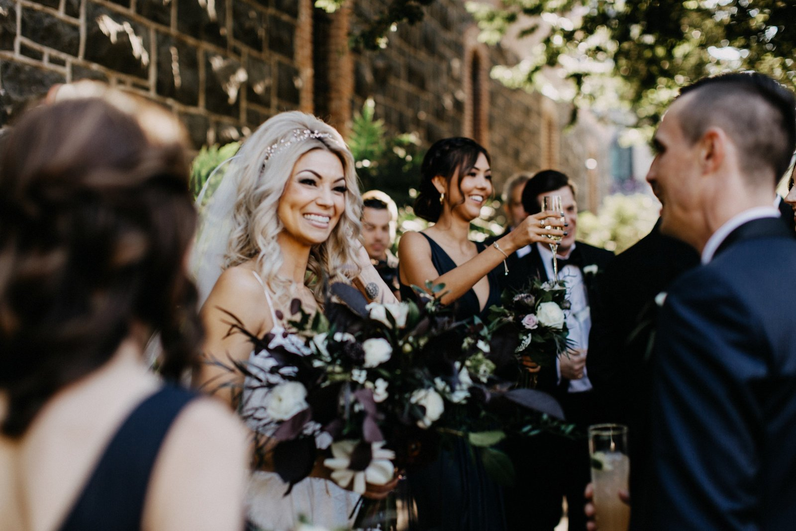 Blonde bride holding bouquet in the city