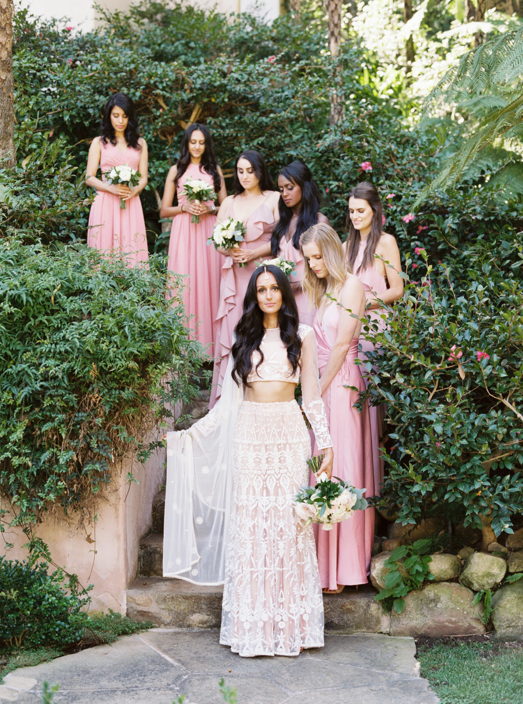 Bride in traditional white wedding saree and bridesmaids in mismatched pink dresses for wedding party photo at Butterfly Lane Estate