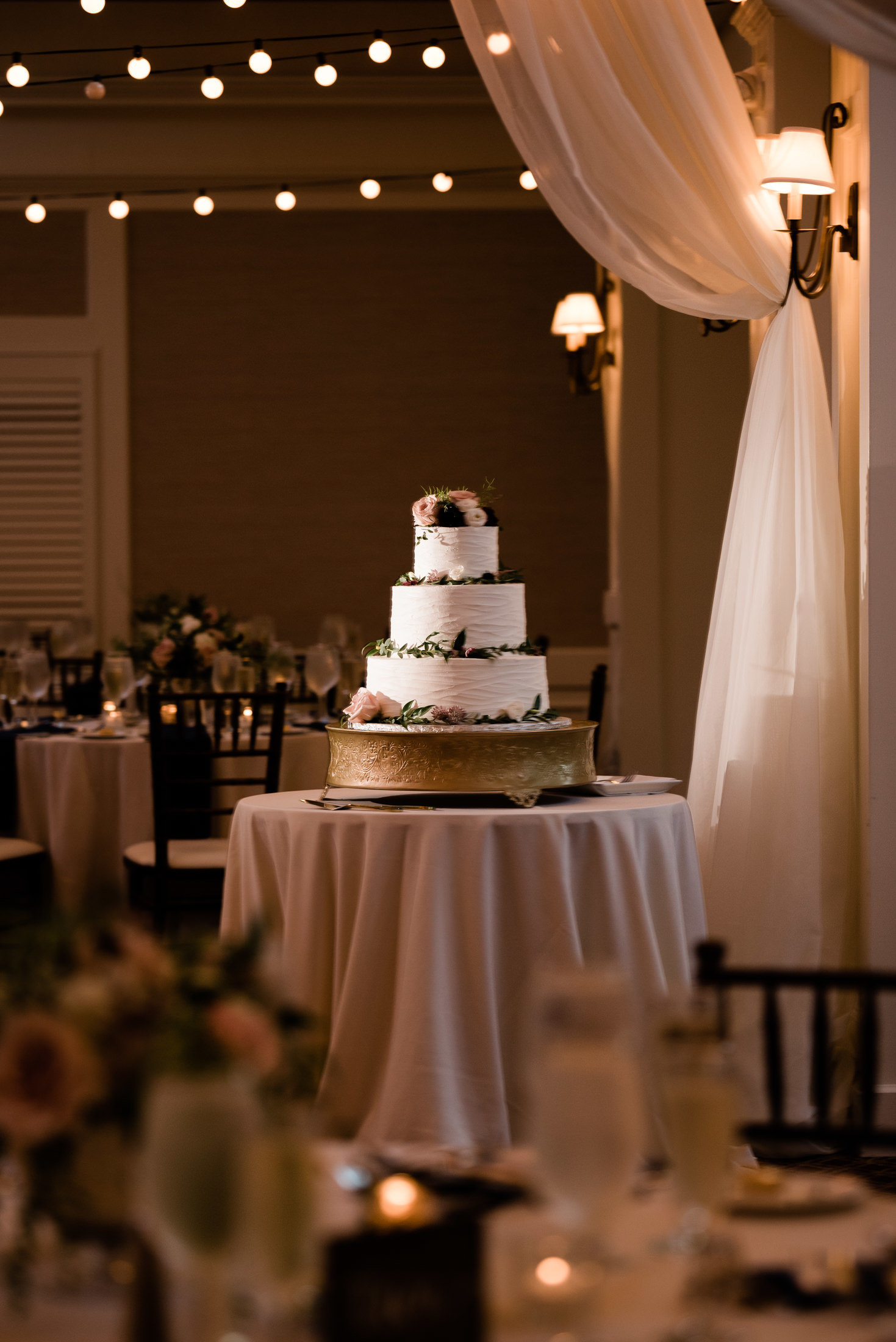 A wedding cake and reception decor shot at a Pavilion at Pinehills wedding
