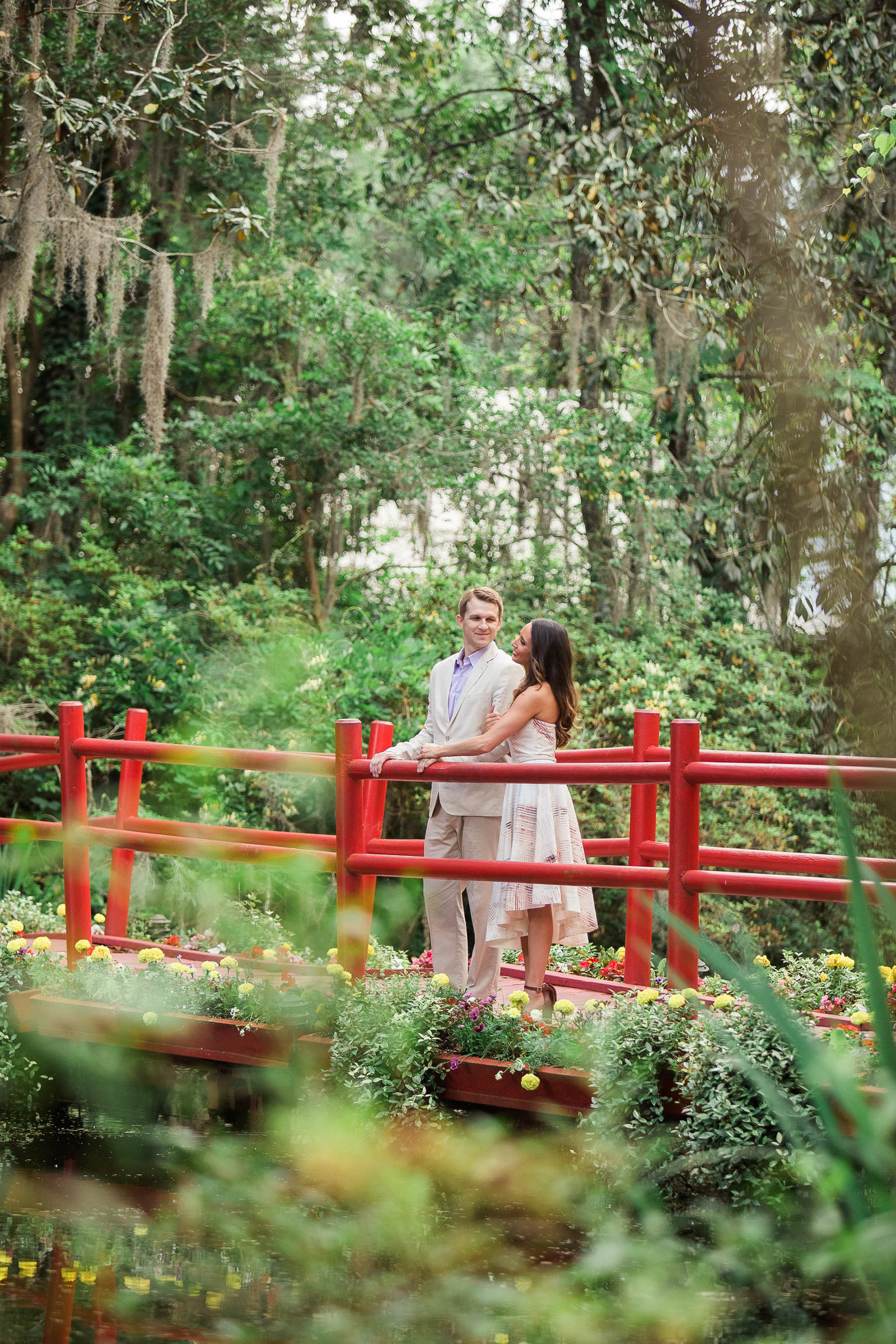 Engaged couple stand on a red bridge, Magnolia Plantation, Charleston, South Carolina