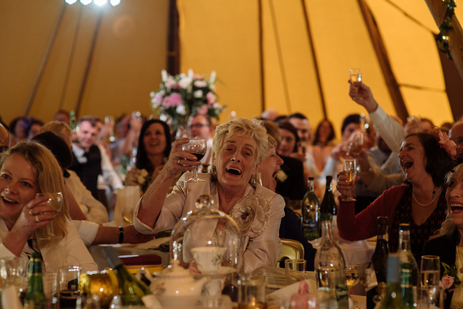 Wedding guests during speeches in tipi at Whelprigg House. Documentary wedding photography